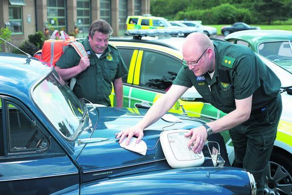 Ambulance responders David England, left, and Dick Tracey give one of their Morris Minors a health check