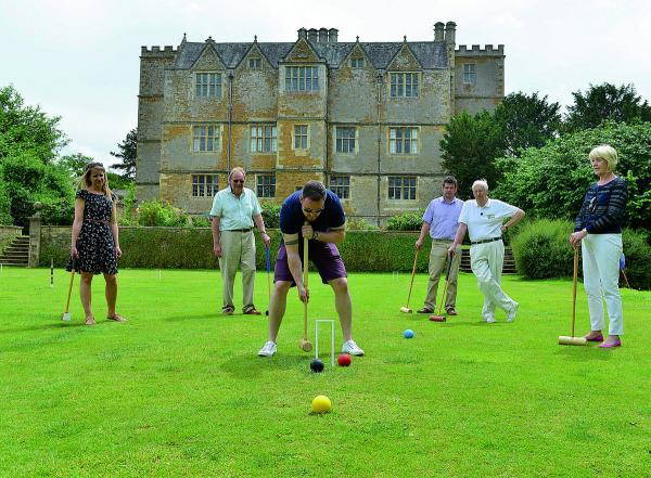 Andy Jones plays croquet at Chastleton House near Chipping Norton on croquet day, from back left to right, Ruth Peters, David Taylor, Ben Jaqu