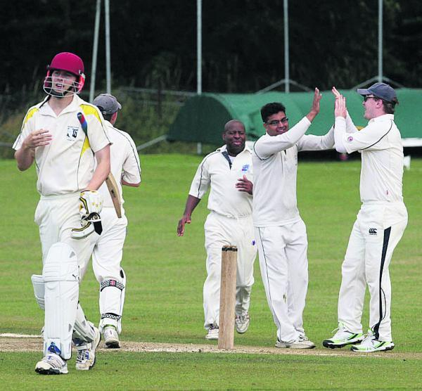 Westcott's Atiq Hussain (second right) celebrates the wicket of David Spencer in their one-wicket loss at Wantage in Division 3                              Picture: Steve Wheeler