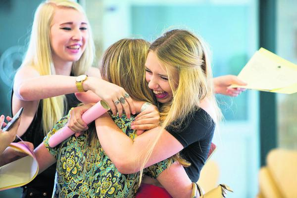 Hugs all round at Witney's Wood Green School, above, as Molly Howlett, left, and Megan Prosser, right, congratulate Becky Brooks
