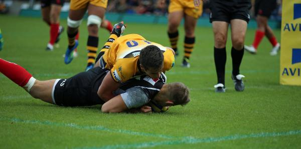 Nick Scott dives over for London Welsh's opening try against Wasps, despite the attentions of Alex Lozowski
