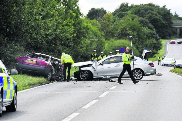 Delays: Police officers investigate the scene of the crash on the A40. The Ford Mondeo, left, and the Mercedes after the crash