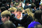 Amelie White, 11, confers with fellow pupils during the quiz