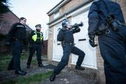 Enforcement: Police officers ram the door of the house in Chorefield during the drugs raid