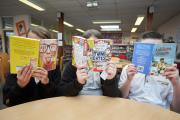 Behind the books are Larkmead School pupils Priti Gurung, Sophie Truby and Harry Wheatley