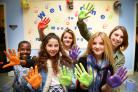 That's handy: Children personalise the refurbished centre with handprints on the walls. From left, Katende Amery, nine, Amber Chainey, 14, Rhiannon Amery,14, Florence Amery, 14, and Katie Dunbar, 14